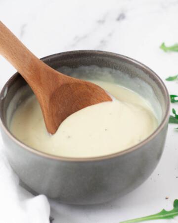 vegan béchamel sauce in gray bowl with wooden spoon