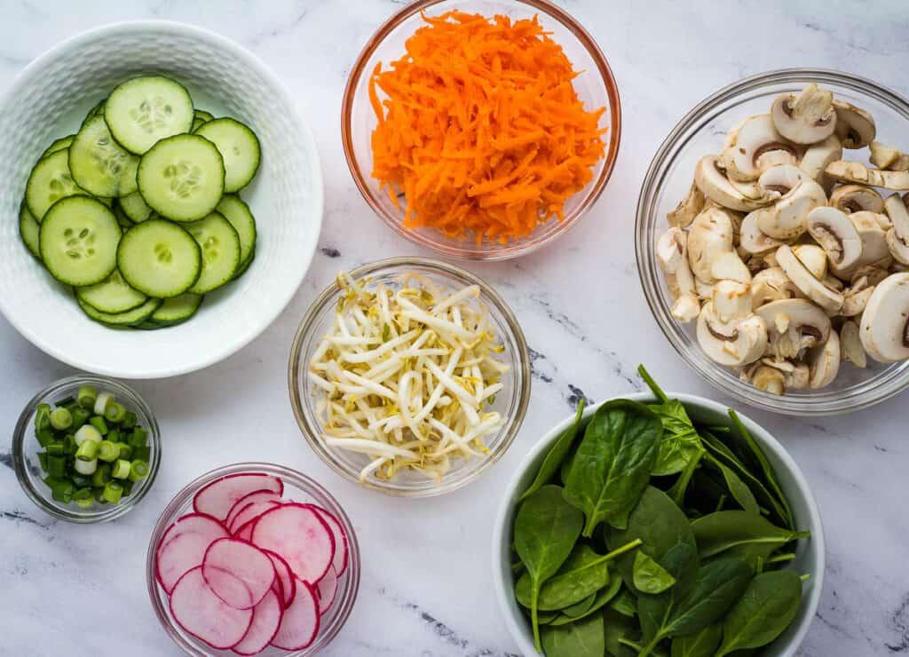 sliced cucumbers in white bowl, shredded carrots in glass bowl, sliced mushrooms in glass bowl, mung beans in glass bowl, spinach in white bowl, sliced radish in glass bowl, sliced scallions in glass bowl