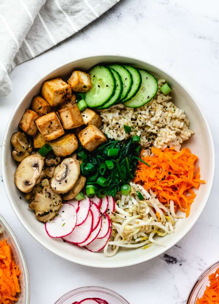 overhead vegan bibimbap with mixed vegetables and baked tofu