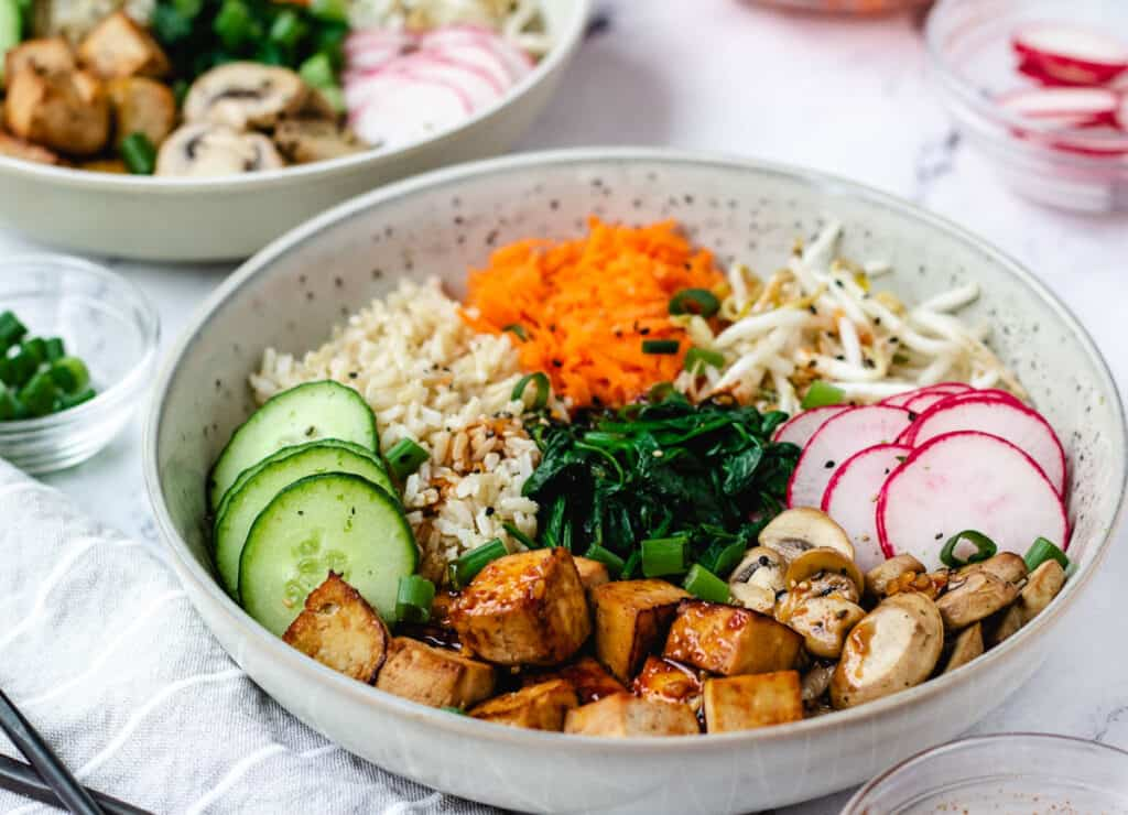close up of vegan bibimbap in gray bowl with mixed vegetables and baked tofu