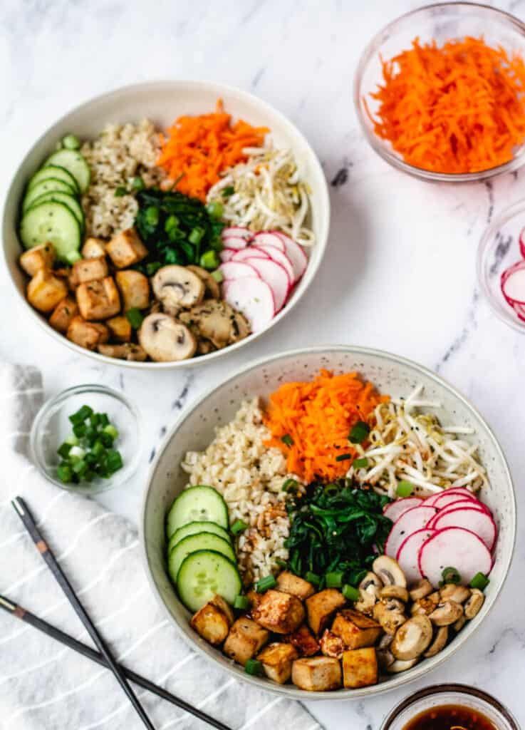 two bowls of vegan bibimbap with chopsticks and bowl of radishes
