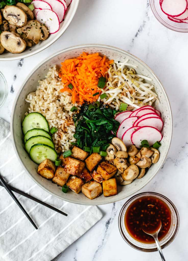 overhead vegan bibimbap with baked tofu, spinach, mushrooms, radishes, mung beans, rice, and cucumber