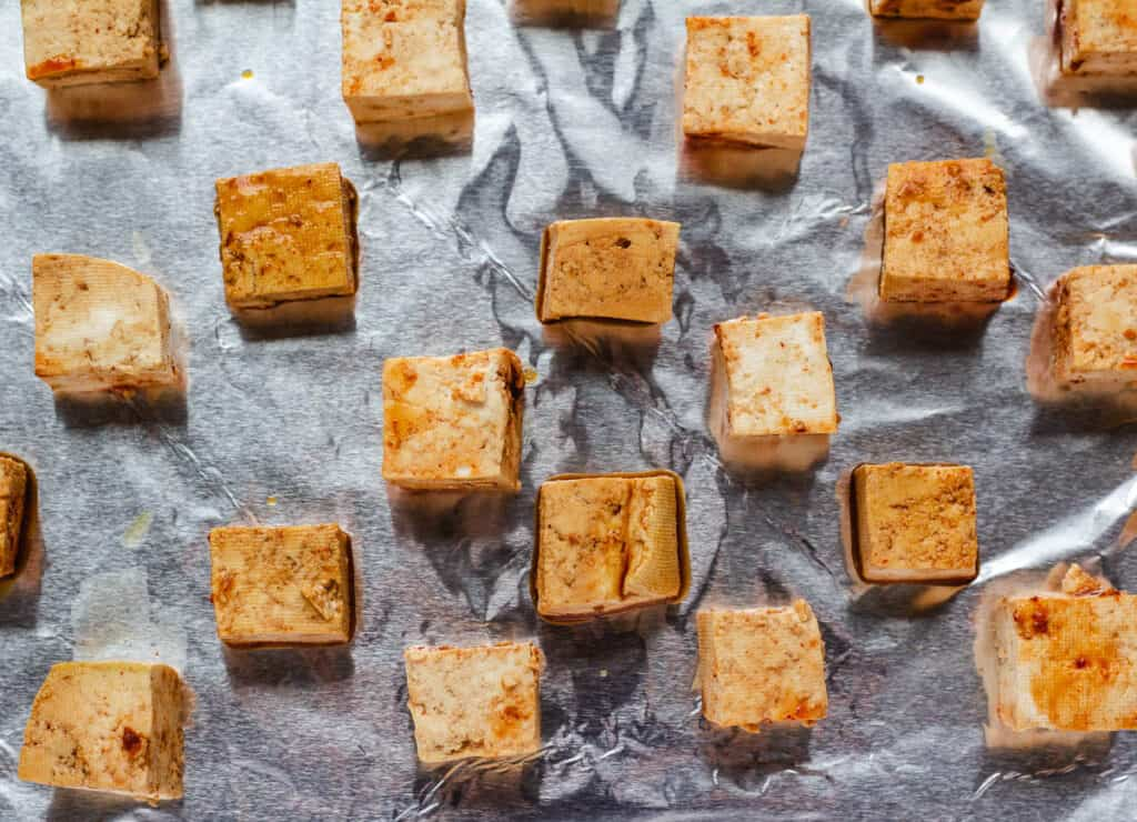 marinated tofu cubes on aluminum lined baking sheet