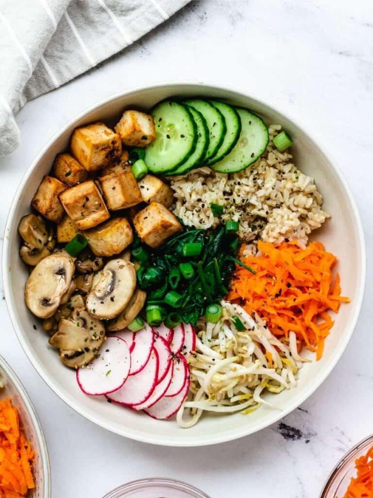 vegan bibimbap in ceramic bowl, with tofu, cucumber, brown rice, carrots, radishes, mushrooms, scallions, and spinach