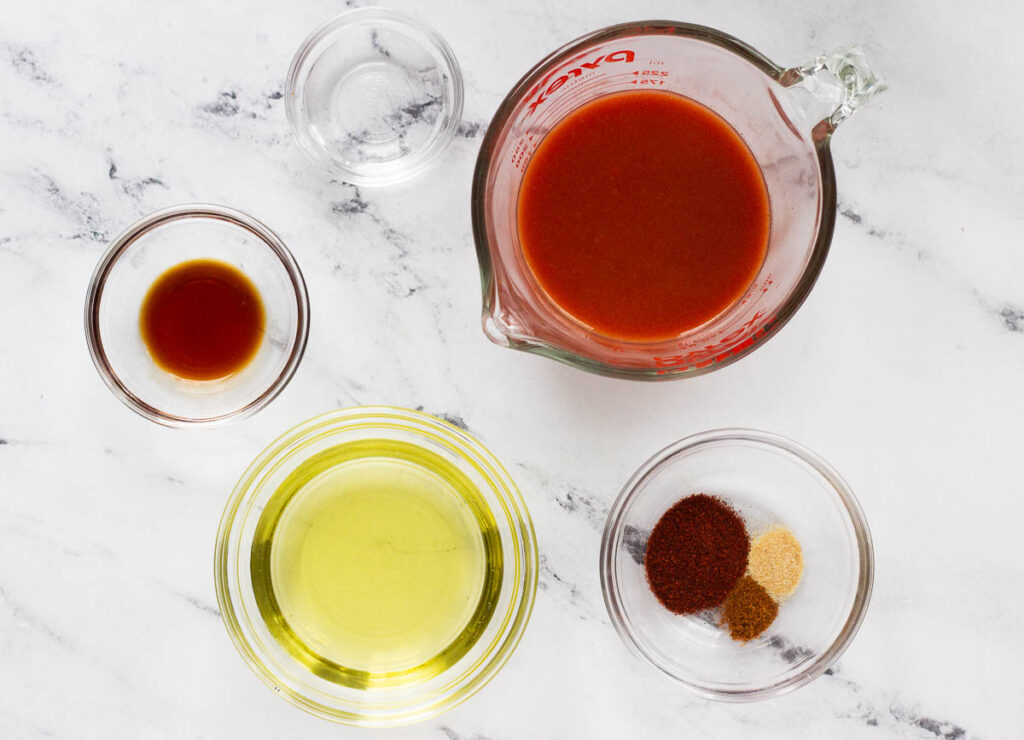 hot sauce, avocado oil, tamari, vinegar, and spices in glass bowls