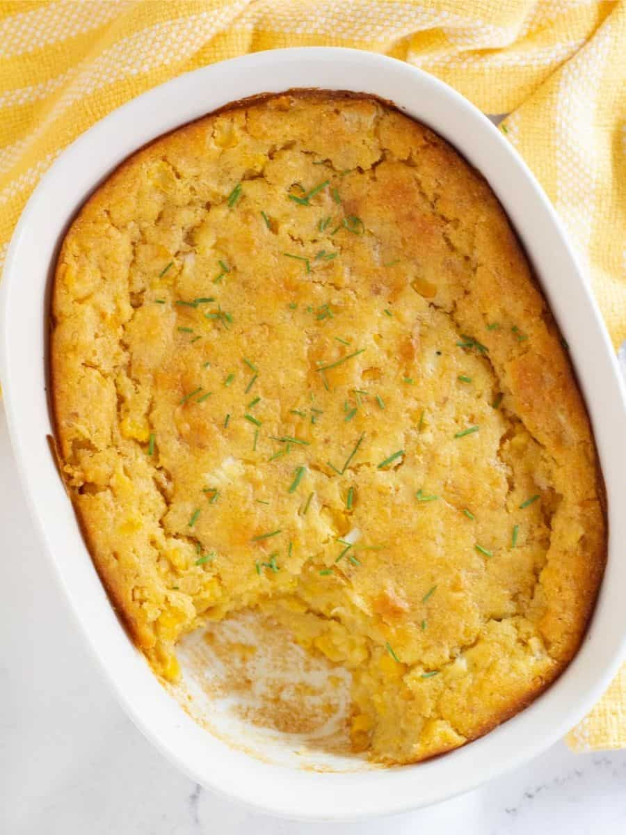 vegan corn casserole in baking dish with serving scooped out
