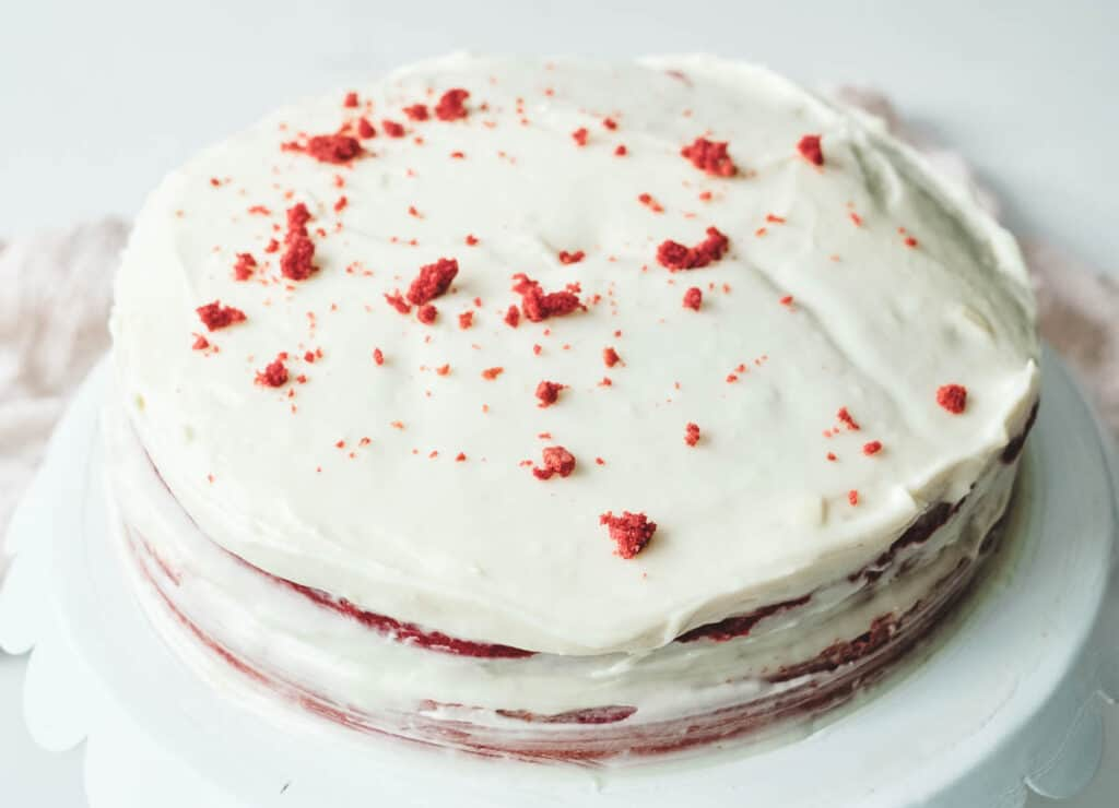 vegan red velvet cake covered in frosting and cake crumbs