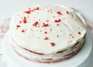 frosted vegan red velvet cake on cake stand