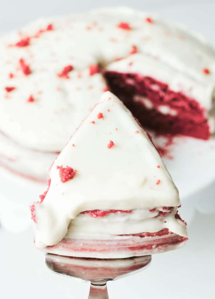 vegan red velvet cake slice overhead with rest of cake in the foreground