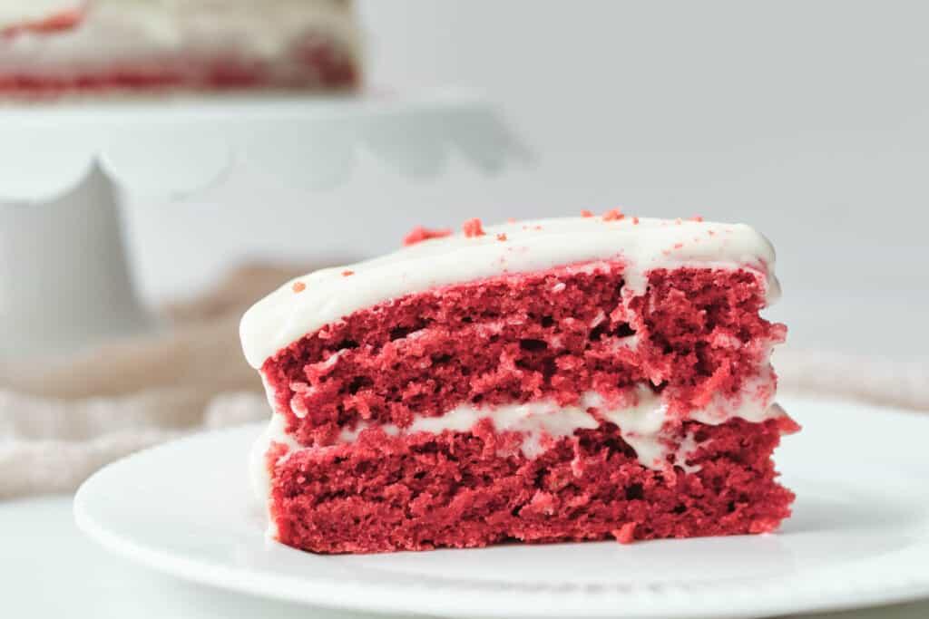 vegan red velvet cake slice on white plate