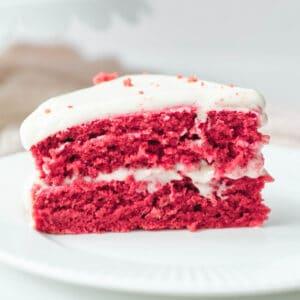slice of vegan red velvet cake with cream cheese frosting