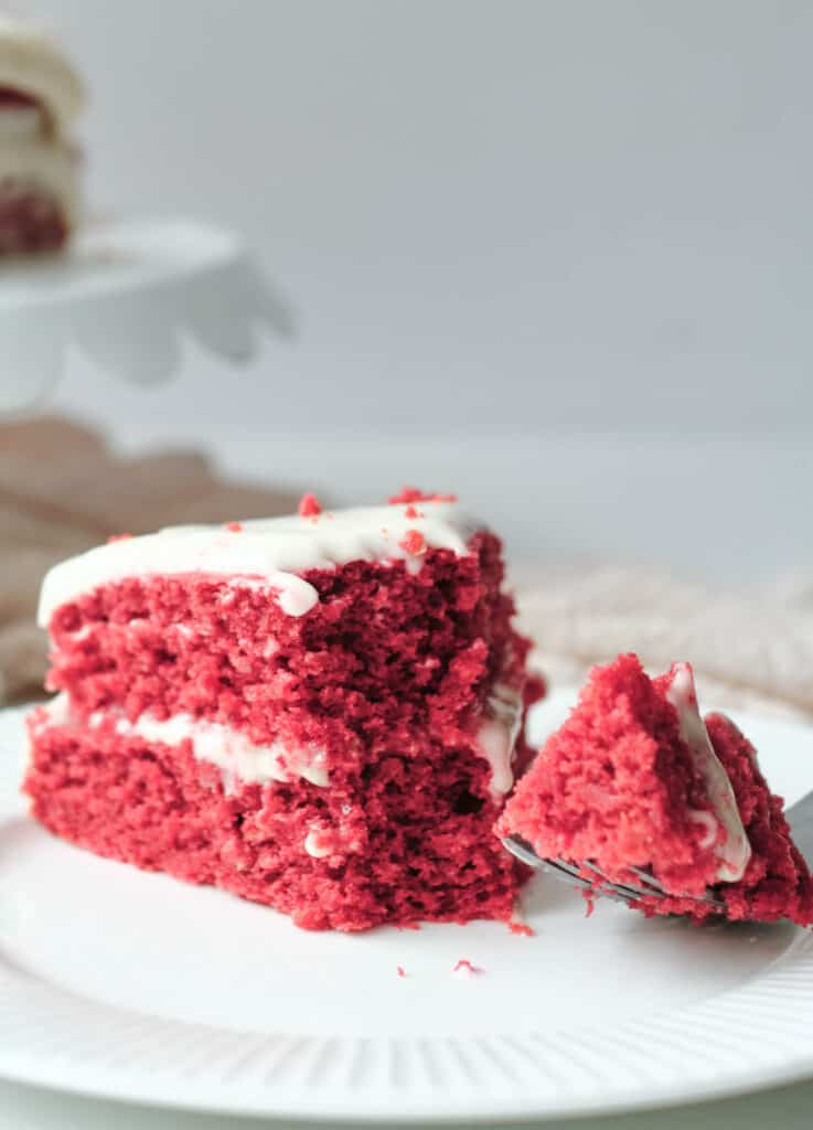 red velvet cake on white plate topped with vegan cream cheese frosting