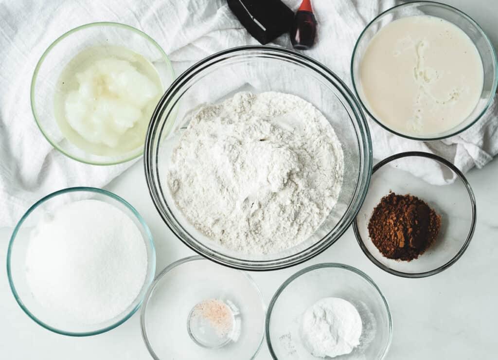 vegan red velvet cake ingredients: flour, vanilla, food coloring, vegan buttermilk, cocoa powder, baking soda, salt, sugar, coconut oil.