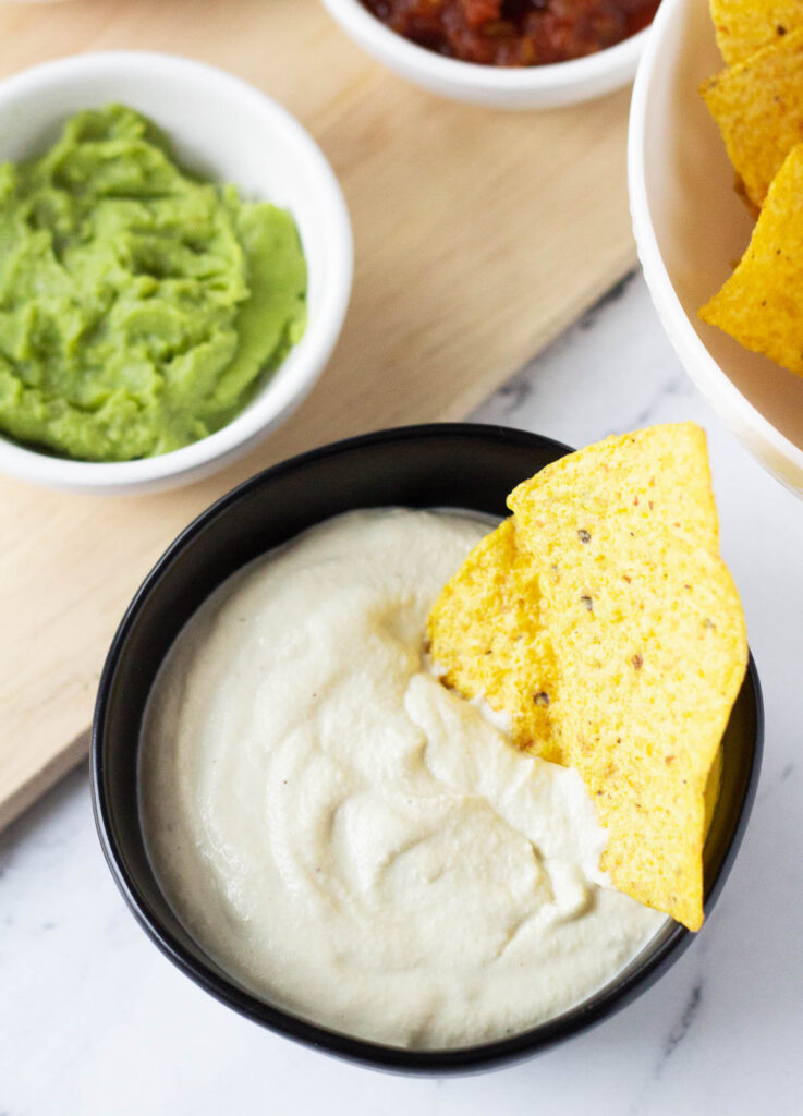 overhead of vegan sour cream with chip dipped inside in black bowl