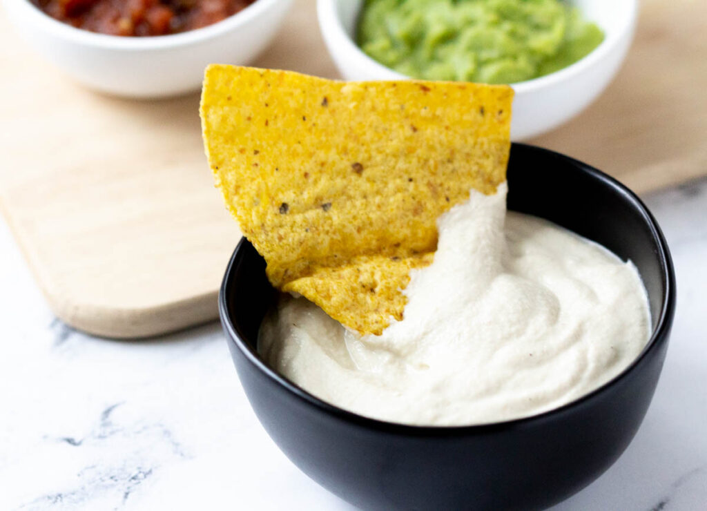 tortilla chip dipped in vegan sour cream in black bowl next to a white bowl of avocado dip and salsa in the background