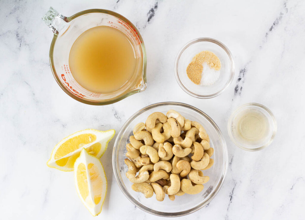 cashews in glass bowl, two wedges of lemon, vegetable stock in measuring cup, apple cider vinegar, and spices in glass bowls