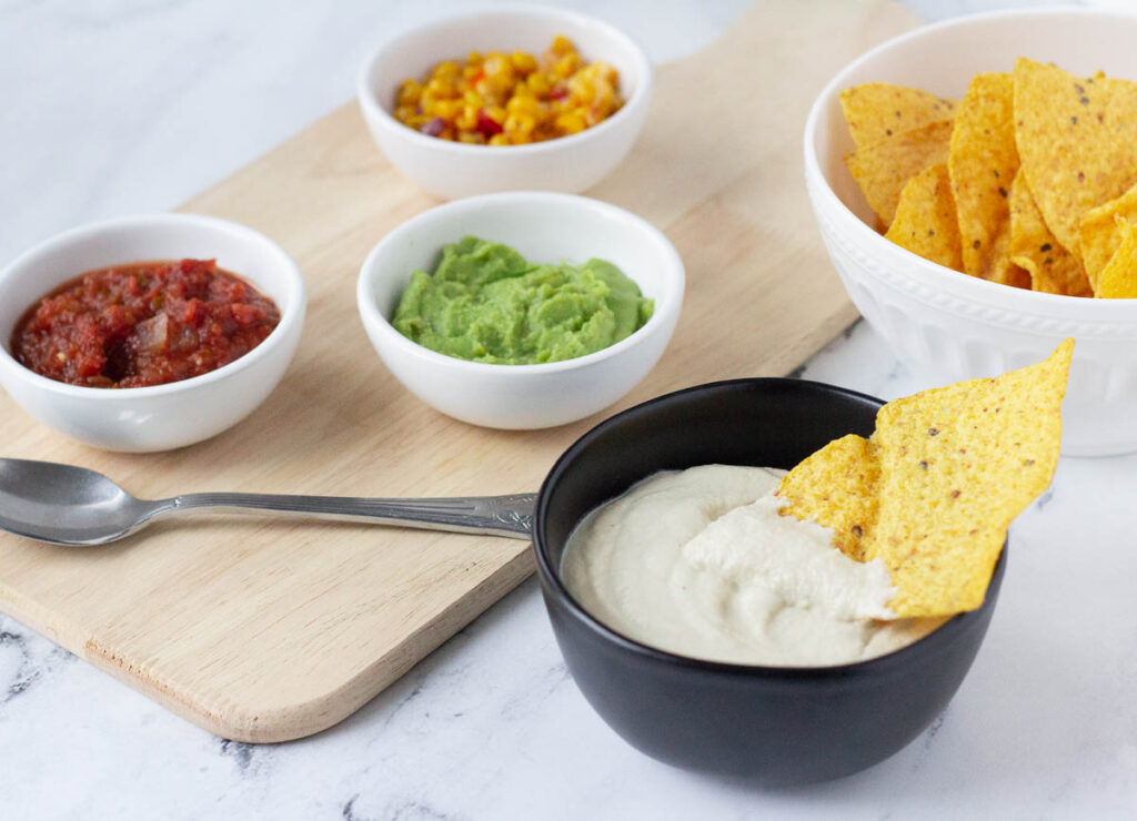chip dipped in vegan sour cream in black bowl, next to a bowl of tortilla chips, and small bowls of salsa, guacamole, and corn salsa on wooden serving tray