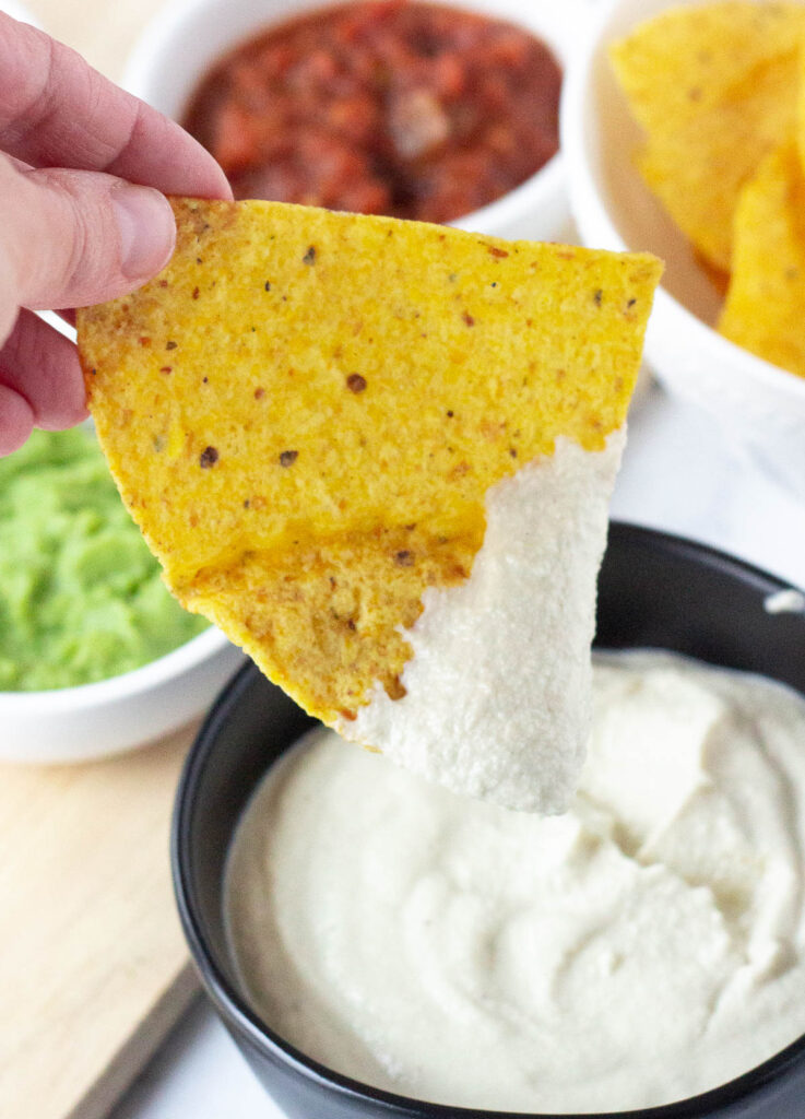 hand holding chip dipped in cashew cream over black bowl filled with vegan cashew sour cream