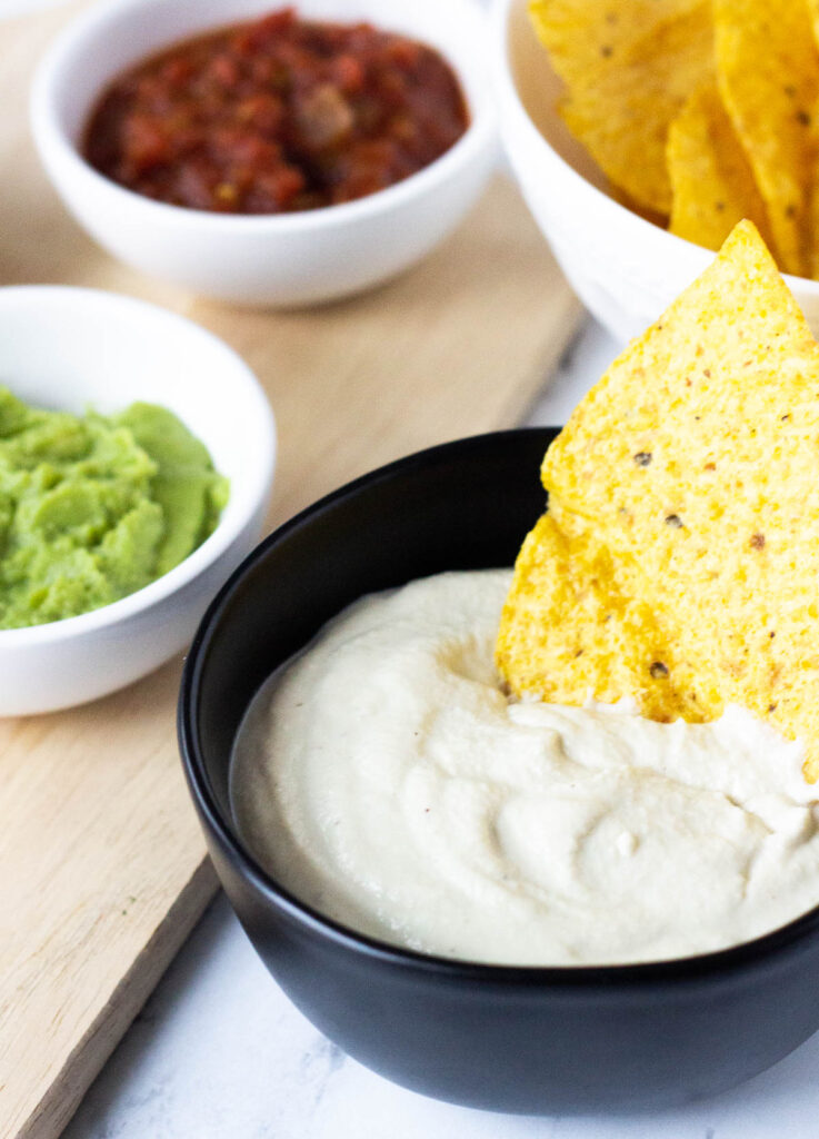 tortilla chip dipped in vegan sour cream in black bowl next to a white bowl of avocado dip