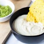 tortilla chip dipped in vegan sour cream in black bowl next to a white bowl of avocado dip