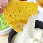hand dipping tortilla chip in vegan sour cream