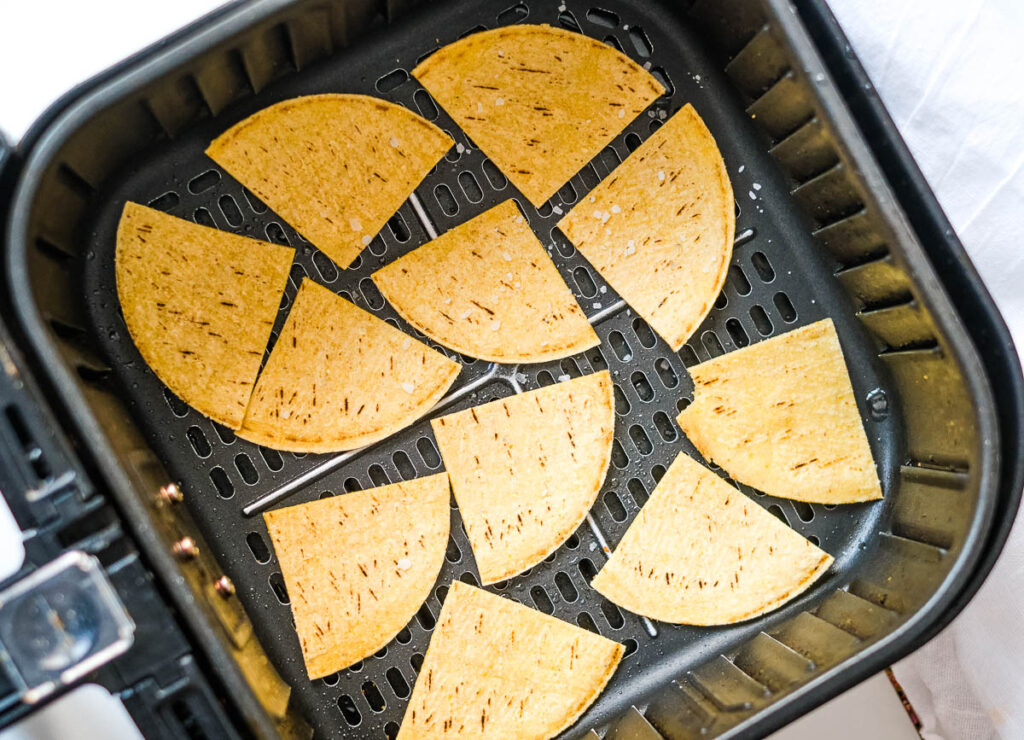 corn tortillas in single layer of air fryer basket, sprinkled with salt