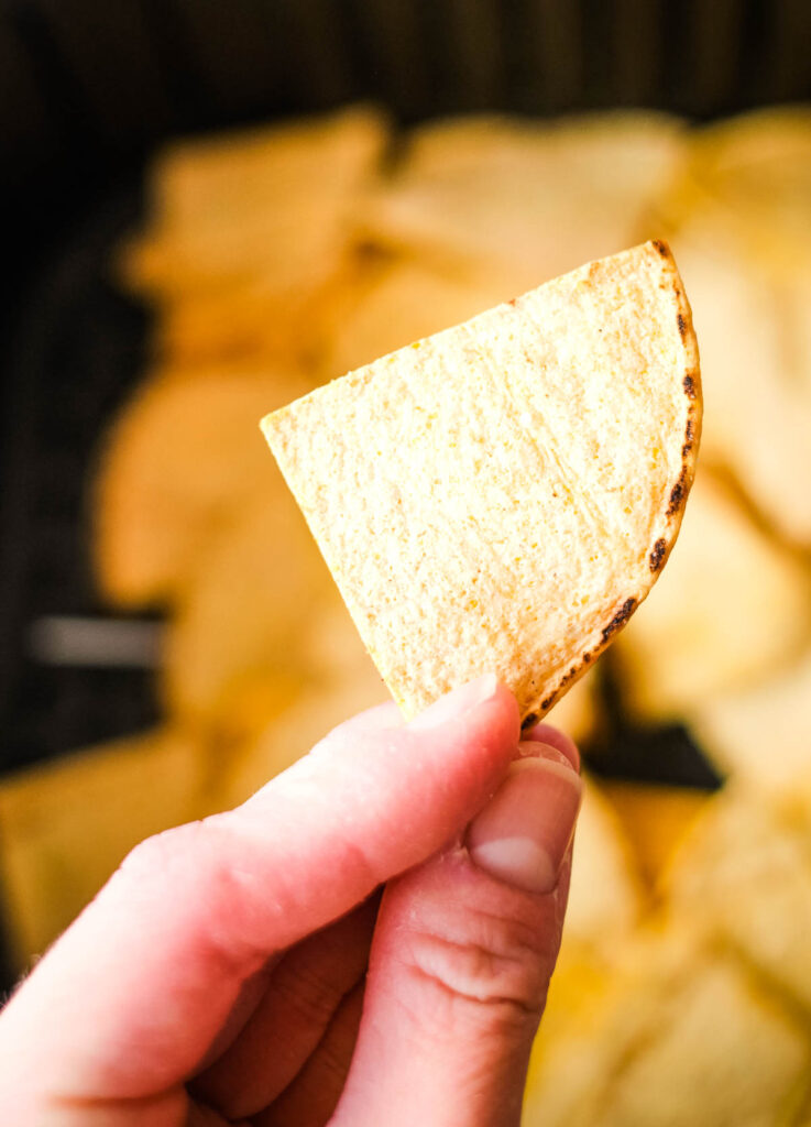 hand holding a crispy air fryer tortilla chip