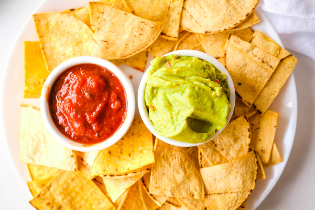 overhead shot of crispy homemade tortilla chips on white bowl served with bowls of salsa and guacamole