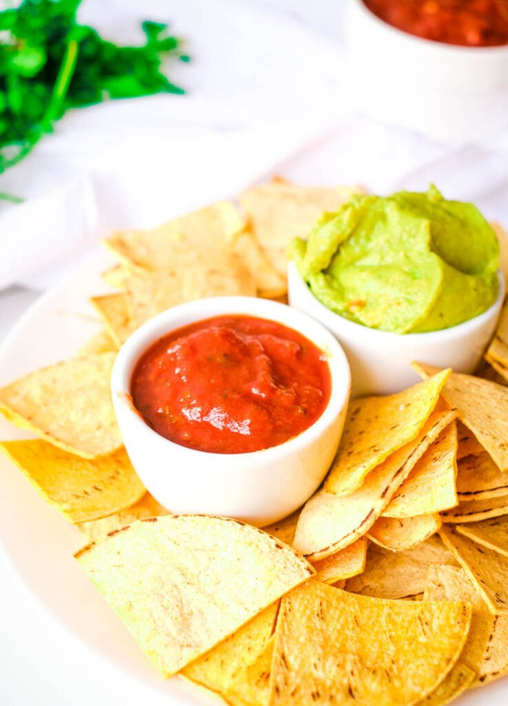 tortilla chips on white plate served with bowls of salsa and guacamole