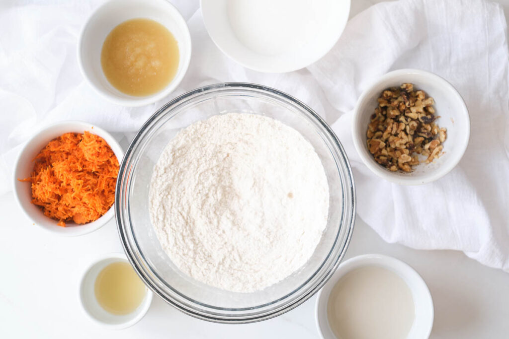 vegan carrot cake cupcake ingredients: shredded carrots, applesauce, almond milk, walnuts, flour