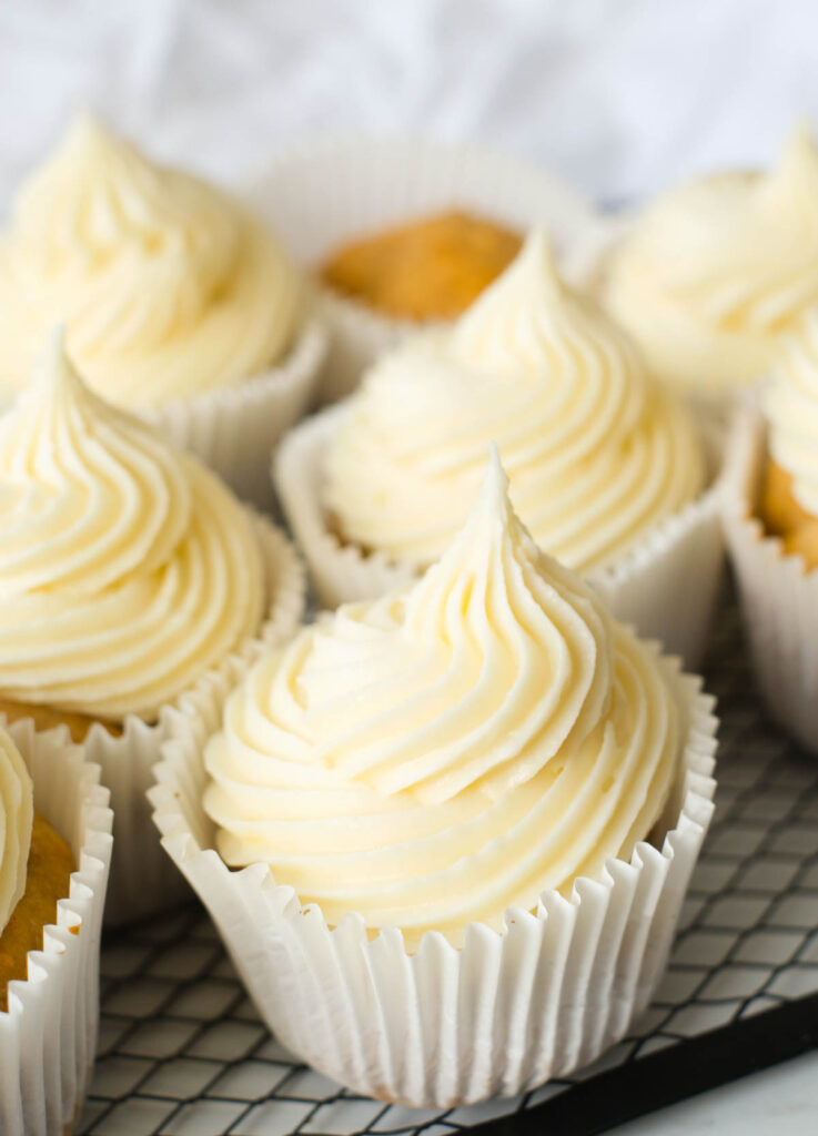 cupcakes with cream cheese frosting on wire rack