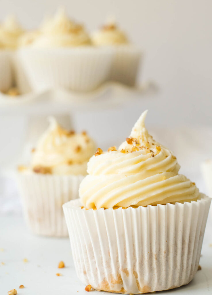 vegan carrot cake cupcakes topped with walnuts