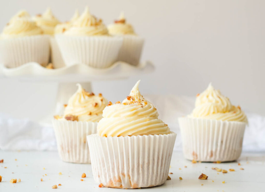 carrot cake cupcakes on white counter topped with cream cheese and chopped walnuts