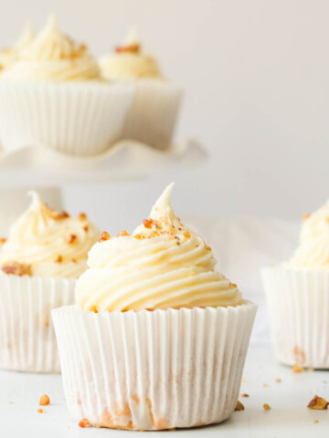 vegan carrot cake cupcakes with cream cheese frosting and chopped walnuts