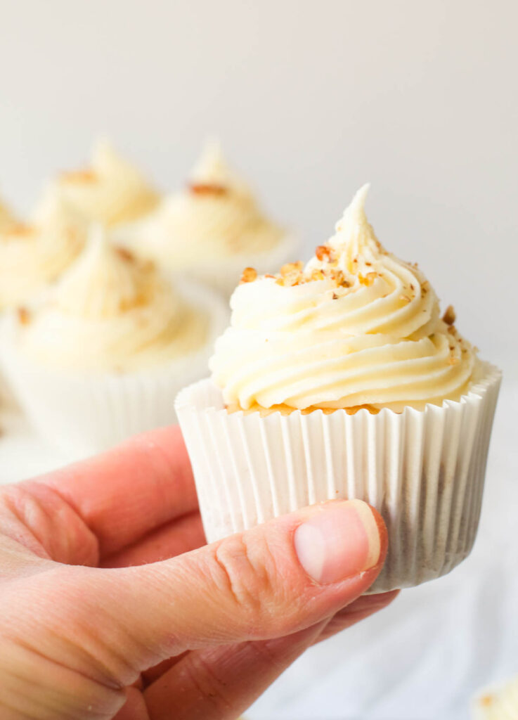 hand holding a vegan carrot cake cupcake with cream cheese frosting and topped with chopped walnuts