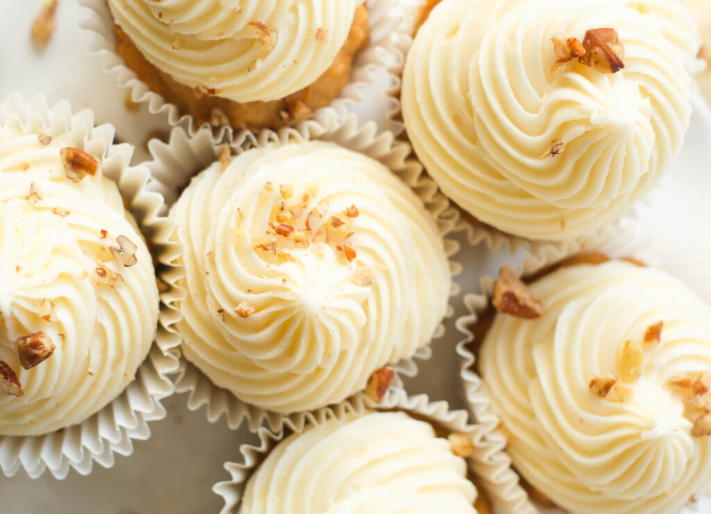 overhead shot of cupcakes with cream cheese frosting topped with chopped walnuts