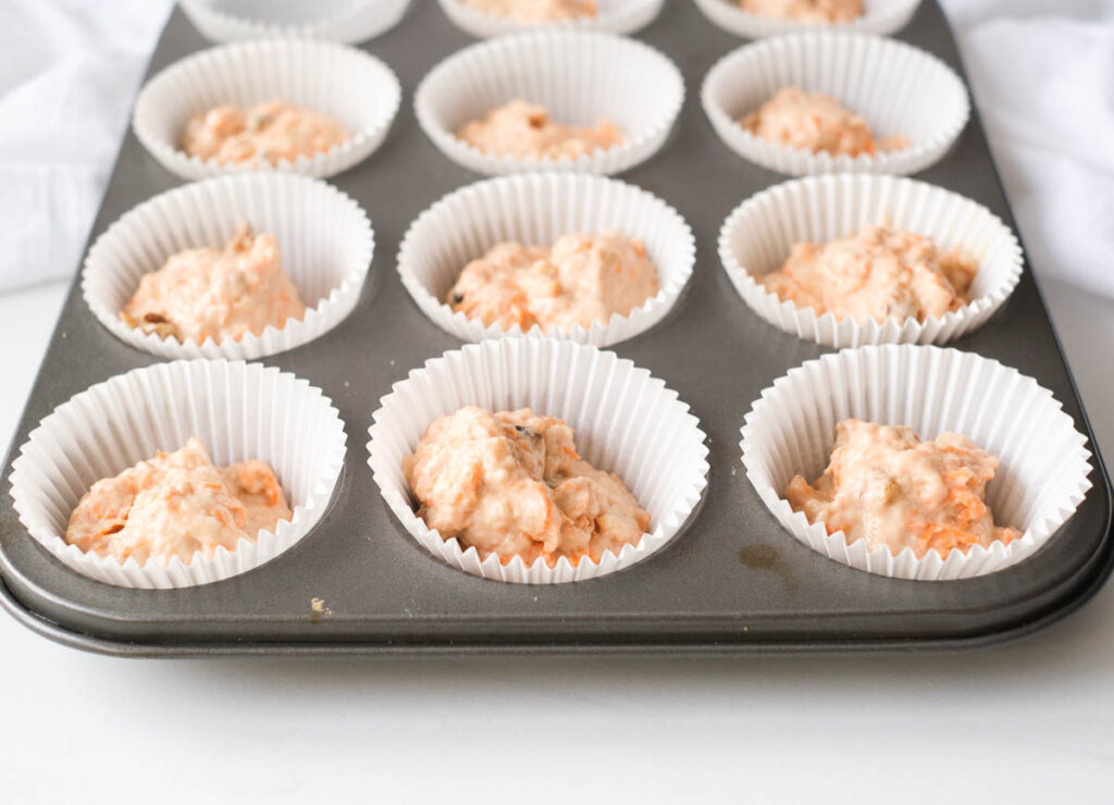 muffin tin filled with carrot cake batter