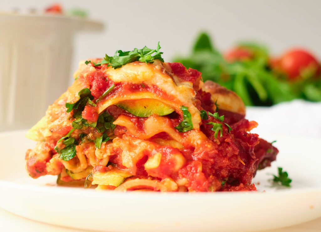 slice of gluten free vegan lasagna on white plate topped with fresh herbs