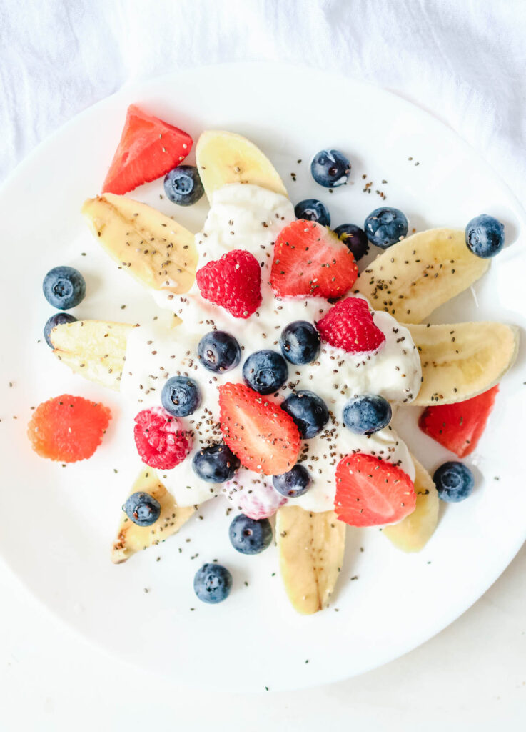white plate topped with sliced bananas, yogurt, fresh berries and chia seeds