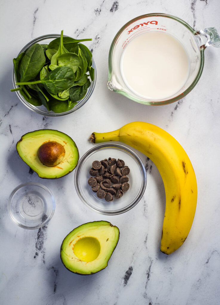 banana, avocado cut in half, peppermint extract, almond milk, and spinach leaves
