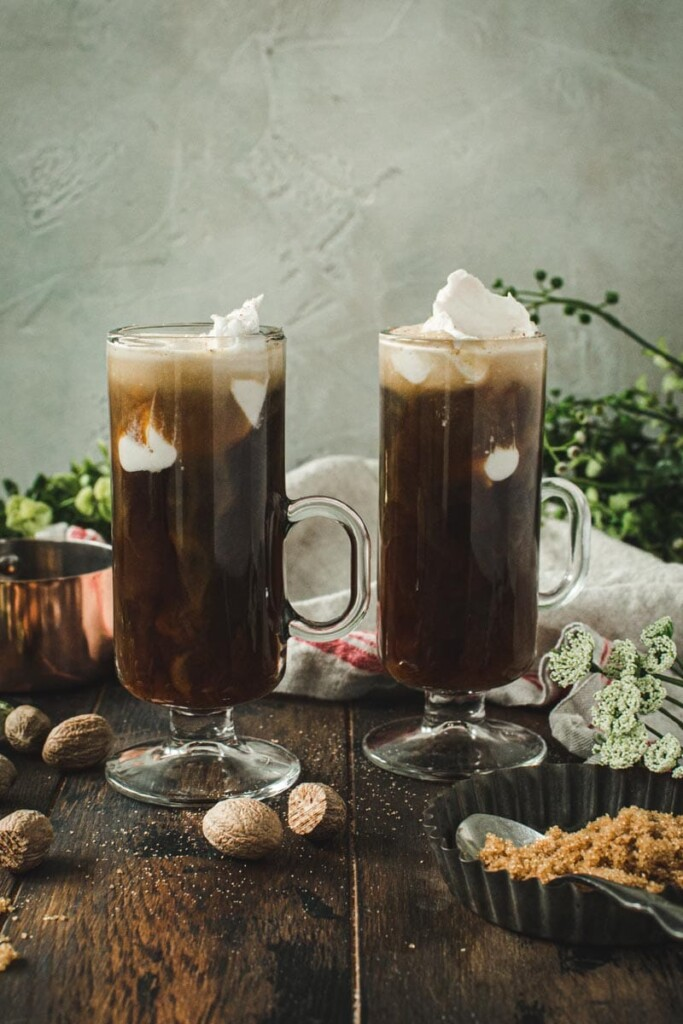 two vegan Irish coffees in glass mugs topped with coconut whipped cream