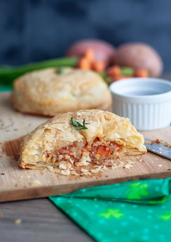 pastry pies filled with veggies on wood cutting board