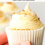 hand holding vegan carrot cake cupcake with cream cheese frosting
