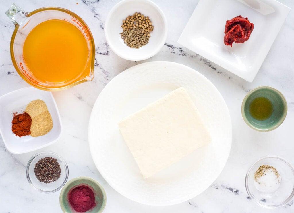 ingredients for vegan corned beef: tomato paste, cumin seeds, coriander seeds, paprika, onion powder, garlic powder, mustard seeds, beetroot powder, salt, pepper, liquid smoke, and tofu