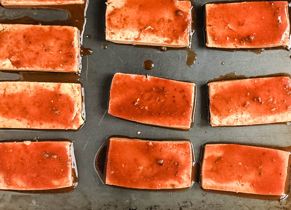 tofu covered with red sauce on baking sheet