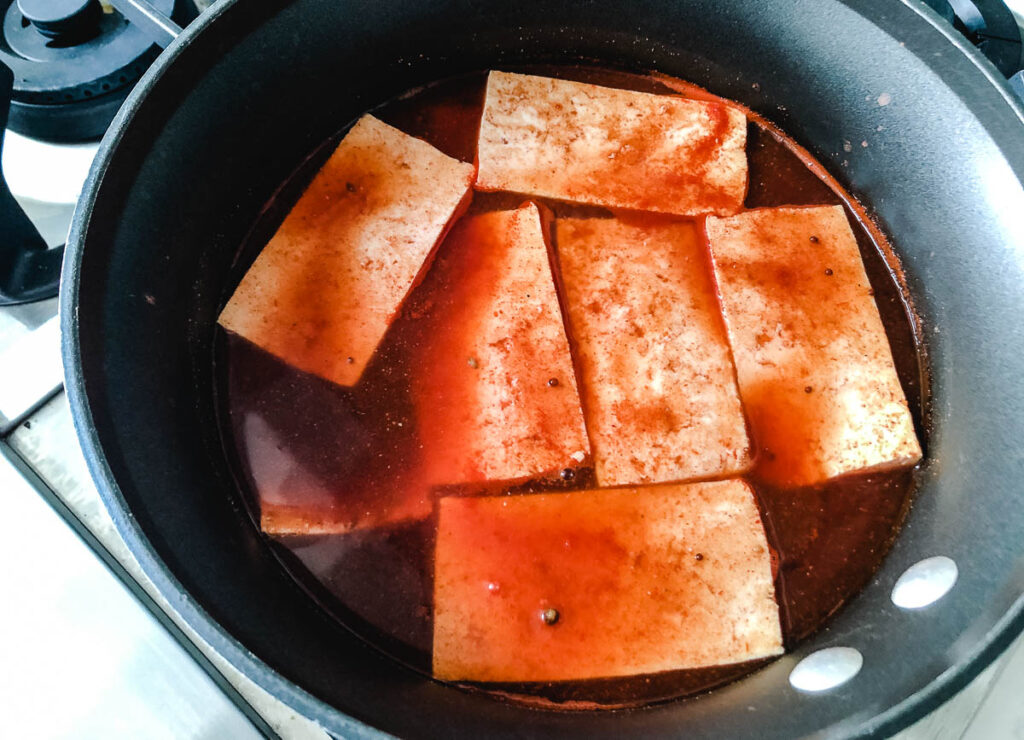 tofu marinating in pot with red sauce