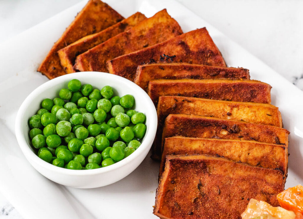 tofu vegan corned beef slices on serving plate with a side of peas