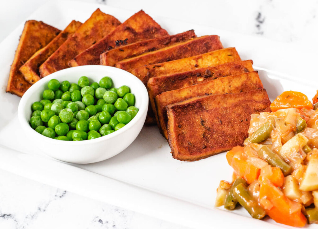 slices of vegan corned beef tofu on white platter with side of peas, potatoes, and carrots