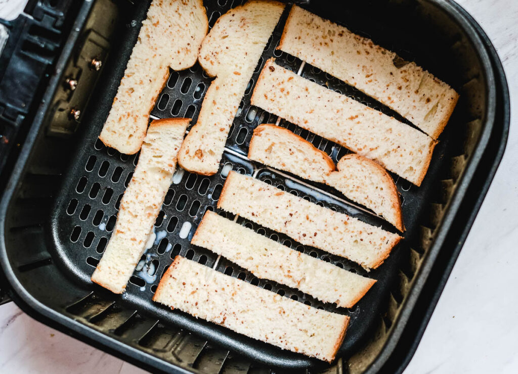 strips of bread dipped in wash in air fryer basket before baked