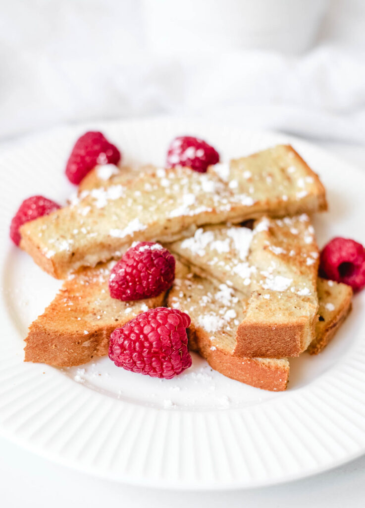 vegan French toast sticks on white plate topped with powdered sugar and fresh raspberries